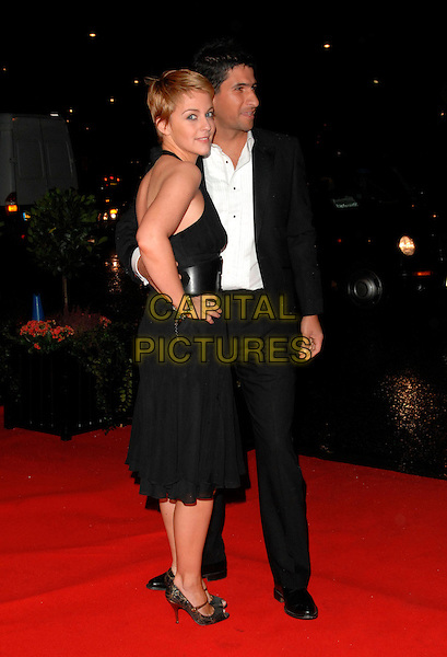 MIRANDA RAISON & GUEST.Variety Club Showbiz Awards at the Park Lane Hilton, London, England. .November 18th 2007.full length black dress looking over shoulder halterneck hand on hip suit .CAP/CAN.©Can Nguyen/Capital Pictures