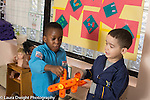 Education Preschool 3-4 year olds two boys playing together with plastic constructions they are using as airplanes