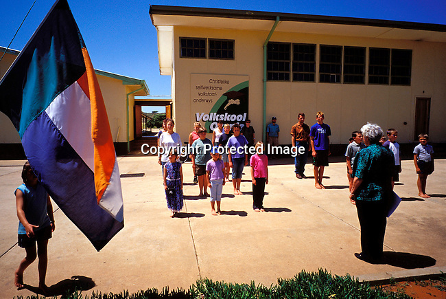 """DIPOAFR00075.Shool children at the """"Volkskool"""" in Orania having a weekly ceremony where the flag is honored.They live in the all white town of Orania where no colored och black people are allowed. Orania is a community of about 600 people where the residents are trying to to preserve Afrikaner culture and language..Photo: Per-Anders Pettersson/ iAfrika Photos."""
