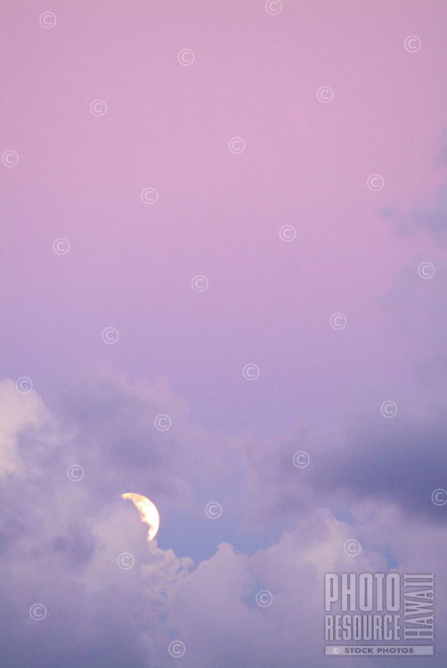 Full moon in a light lavender sky with puffy soft clouds