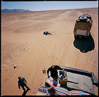 Sahara desert, Libya-Chad, November/December 2004..Every week, a convoy of 40 privately owned Libyan trucks loaded by the WFP with about 1000 metric tons of western food aid cross 2500 km of deep desert across Libya and Chad to reach more than 200 000 refugees from Darfur in camps near the Sudanese border. A lunch stop in the desert, food supply for up to a month is carried on the truck cabin roof.