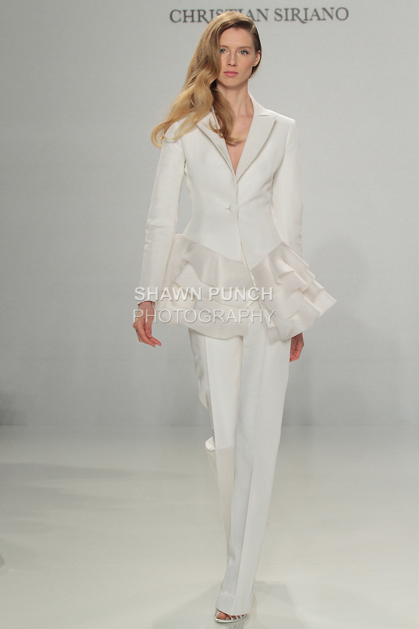 Model walks runway in a tailored suit with cascading ruffles, from the Christian Siriano for Kleinfeld bridal collection, at Kleinfeld on April 18, 2016 during New York Bridal Fashion Week Spring Summer 2017.