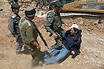 An IDF soldier throws an activist to the ground after he resisted arrest while other soldiers look on at a construction site for Israel's controversial West Bank barrier in Beit Jala, near Bethlehem, on Sunday May 23th 2010. Palestinian, Israeli & International activists held up construction work for a short period of time with a non violent demonstration.