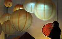 "Kelly.Jordan@jacksonville.com--011512--The Vietnamese Association of Jacksonville marked Vietnam's largest and most important festival, known as ""Tet, "" Sunday at the Jacksonville Fairgrounds. A visitor to the popular festival checks out a display of traditional paper lanterns and umbrellas during the event which featured a fasjhion show, traditional food and music. Mayor Alvin Brown also attended the event.(The Florida Times-Union, Kelly Jordan)"