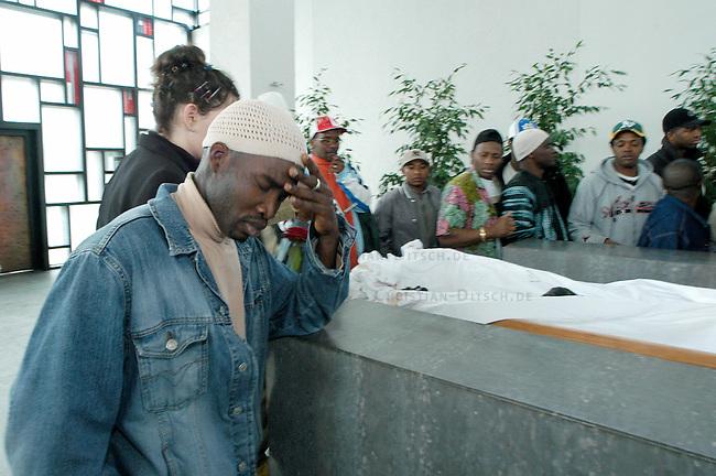 Trauerfeier fuer Oury Jalloh in Dessau<br /> Am 7. Januar 2005 verbrannte in einer Dessauer Polizeiwache unter ungeklaerten Umstaenden der Fluechtling Oury Jalloh. Der 21jaehrige Mann aus Sierra Leone soll sich laut Polizeiangaben im gefesselten Zustand mit einem Feuerzeug selber entzuendet haben.<br /> Hier: Ein freund Jallohs trauert am Sarg in der Trauerhalle des Dessauer Zentralfriedhof.<br /> 26.3.2005, Dessau<br /> Copyright: Christian-Ditsch.de<br /> [Inhaltsveraendernde Manipulation des Fotos nur nach ausdruecklicher Genehmigung des Fotografen. Vereinbarungen ueber Abtretung von Persoenlichkeitsrechten/Model Release der abgebildeten Person/Personen liegen nicht vor. NO MODEL RELEASE! Nur fuer Redaktionelle Zwecke. Don't publish without copyright Christian-Ditsch.de, Veroeffentlichung nur mit Fotografennennung, sowie gegen Honorar, MwSt. und Beleg. Konto: I N G - D i B a, IBAN DE58500105175400192269, BIC INGDDEFFXXX, Kontakt: post@christian-ditsch.de<br /> Bei der Bearbeitung der Dateiinformationen darf die Urheberkennzeichnung in den EXIF- und  IPTC-Daten nicht entfernt werden, diese sind in digitalen Medien nach &sect;95c UrhG rechtlich geschuetzt. Der Urhebervermerk wird gemaess &sect;13 UrhG verlangt.]