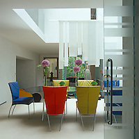 This contemporary double-height dining room has walls of smooth limestone, a tranquil backdrop for the set of colourful chairs with which it has been furnished
