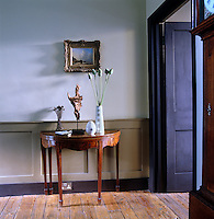 An 18th century demilune and a 19th century painting by Abraham Hulk on the main floor landing