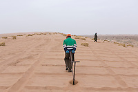 Chinese afforestation workers prepare the ground before poking straw partway into the sand, forming a pattern of small squares in the desert areas of Minqin county in Gansu province, October 2016. The grid like network of straw fences break the force of the wind at ground level, stopping dune movement by confining the sand within the squares of the grid. Minqin county is located in between the Tengger Desert and the Badain Jaran Desert.