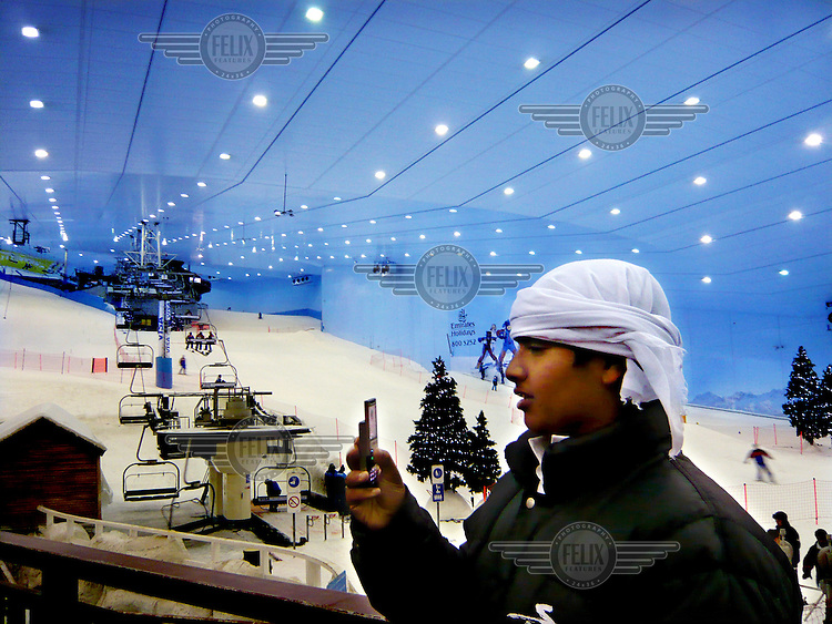 A young visitor to Ski Dubai, situated inside the Mall of Emirates (the largest shopping mall in the world), takes a photograph on his mobile phone. The huge indoor ski centre has vast temerature control and insulation systms to keep the temperature between -1 and -6 degrees centigrade, while the outside temperature soars between 35 and 50 degrees centigrade.