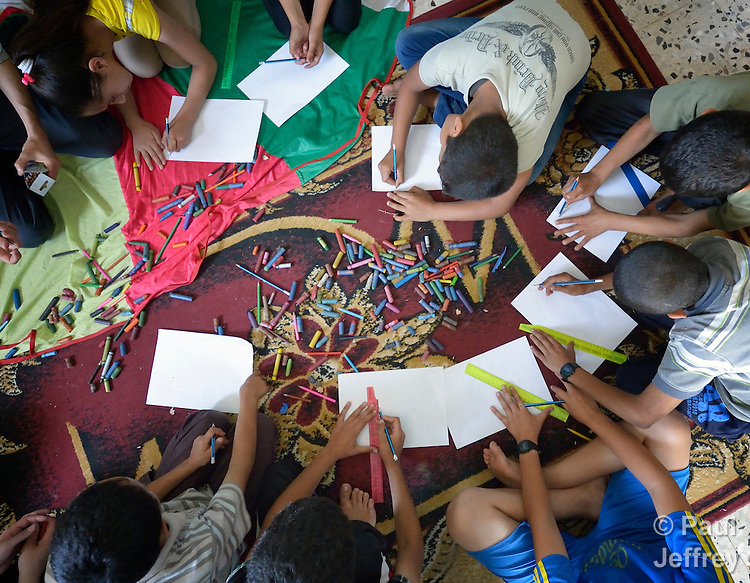 Children draw during an activity at the Youth Empowerment Center in Beit Hanoun, Gaza. The program is supported by Caritas and DanChurchAid, a member of the ACT Alliance, and is designed to help children better cope with the trauma they experienced during the 2014 war.<br /> <br /> In the wake of that war between the government of Gaza and the government of Israel, ACT Alliance members are supporting health care, vocational training, rehabilitation of housing and water systems, psycho-social care, and other humanitarian actions throughout the besieged Palestinian territory.