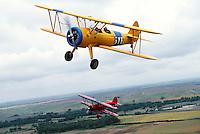 Aerial view of vintage Stearman biplanes in flight.