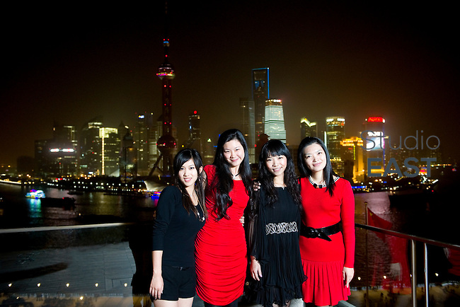 From left to right: FENG Bo 'Candice', ZHOU Lili 'Lillian', LIU li 'Helene', and YAO Jinchen 'Miley' pose for a group photo from Sir Elly's bar, Peninsula hotel, in front of the Pudong skyline, in Shanghai, China, on November 13, 2010. Thanks to the Peninsula for the help. Photo by Lucas Schifres/Pictobank