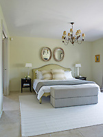 The simple cream, white and grey colour scheme of the master bedroom is complemented by notes of gold from a gilt-framed painting and antique chandelier hanging above the bed