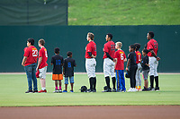 A group of young baseball players join Kannapolis Intimidators outfielders Jameson Fisher (11), Joel Booker (23), and Micker Adolfo (27) on the field for the National Anthem prior to the game against the West Virginia Power at Kannapolis Intimidators Stadium on June 17, 2017 in Kannapolis, North Carolina.  The Power defeated the Intimidators 6-1.  (Brian Westerholt/Four Seam Images)