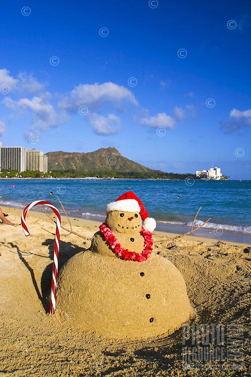 Santa sandman with candycane, lei and santa cap on Waikiki beach with Diamond head, Oahu