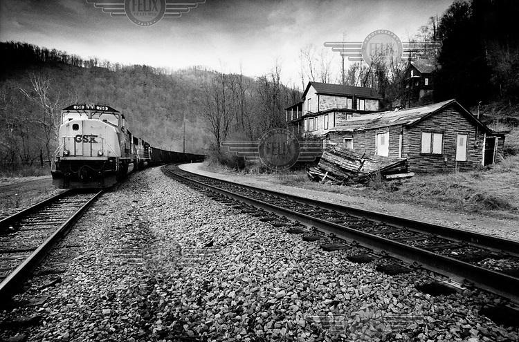 USA. West-Virginia, Thurmond, april 2003..Beeld van een ghost town, een verlaten dorp in de steenkoolstreek..Een trein rijdt langs verkrotte huizen. Door de grote werkloosheid en de sluiting van de koolmijnen emigreerde de bevolking en werd Turmond een Ghost town.foto: Tim Dirven/HH..USA. West-Virginia, Thurmond, April 2003..View of a ghost town..Train passing dilapidated houses. Because of the closing down of miningcompanies, people fled unemployment and Thurmond became a ghost town..Photo: Tim Dirven/Panos Pictures....