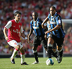 Inter Milan's Adriano tussles with Arsenal's Cesc Fabregas. .Pic SPORTIMAGE/David Klein