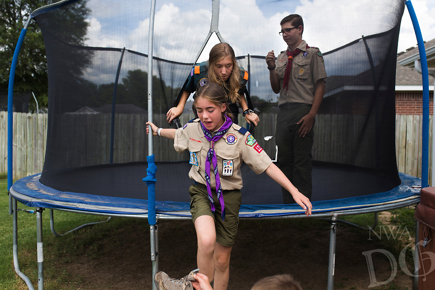 NWA Democrat-Gazette/CHARLIE KAIJO Ruby Freeman (center) gets out of a trampoline with sister Isa (back) and Matthew (right), Saturday, July 14, 2018 at their home in Bentonville.