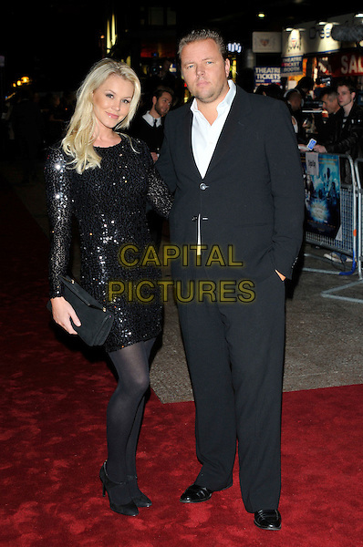 """AMY GUY & GUEST.Attending the UK film premiere of """"The Imaginarium Of Doctor Parnassus"""" at the Empire Leicester Square cinema, London, England, UK, October 6th 2009..full length black sequined sequin dress tights suit shoes clutch bag.CAP/PL.©Phil Loftus/Capital Pictures."""