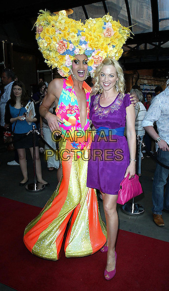 "CAST MEMBER & SARAH MANNERS.""Priscilla: Queen Of The Desert The Musical"" - Cast Change, London, England, UK..June 22nd, 2010.arrivals full length purple dress peep toe shoes drag queen hat character costume yellow flowers pink bag purse blue belt.CAP/WIZ.© Wizard/Capital Pictures."