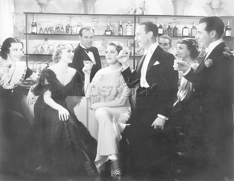 Elegant group of people at a bar toasting a woman