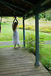 Blonde woman standing on porch looking out