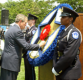 Washington, DC - May 15, 2004 -- United States President George W. Bush places a flower in the memorial wreath at the Annual Peace Officers' Memorial Service on the West Lawn of the United States Capitol in Washington, D.C. on May 15, 2004.  The service, sponsored by the Fraternal Order of Police (FOP), is held annually on May 15 to honor those who gave their lives during the previous year and to honor their families.  The service remembers the sacrifice of the more than 15,000 officers who have been killed in the line of duty since 1794.<br /> Credit: Ron Sachs / CNP<br /> (RESTRICTION: NO New York or New Jersey Newspapers or newspapers within a 75 mile radius of New York City)
