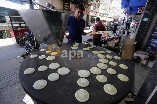 A Palestinian vendor prepares traditional pancakes known as ''Qatayef'' on the holy month of Ramadan at market in Gaza city on May 27, 2017. Ramadan is sacred to Muslims because it is during that month that tradition says the Koran was revealed to the Prophet Mohammed. The fast is one of the five main religious obligations under Islam. More than 1.5 billion Muslims around the world will mark the month, during which believers abstain from eating, drinking, smoking and having sex from dawn until sunset. Photo by Mohammed Asad