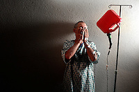 An older man with an gas can connected to an intravenous IV cord stands in a hallway.