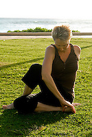 A woman practices yoga on the grass at Queens Beach Park in Waikiki.