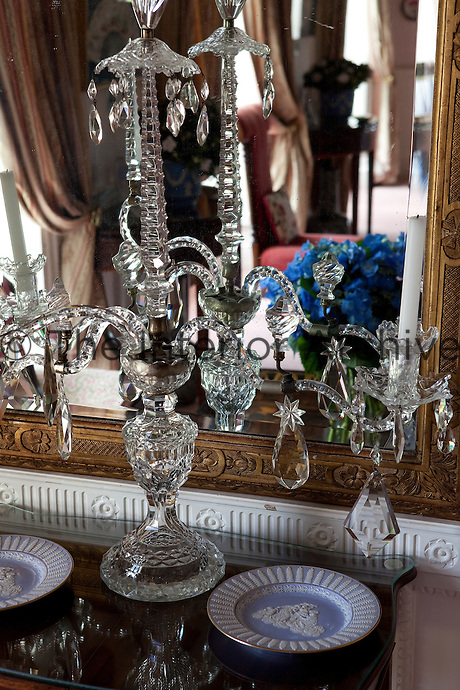 A crystal candelabra on a side table in the drawing room is reflected in a gilt-framed mirror