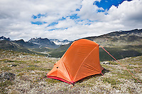 Backpacking tent in mountain landscape with Memurudalen in background, Jotuhnehimen national park, Norway