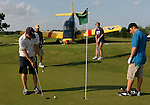Brian Criswell (left) doesn't let a nearby crashed airplane disrupt his golf game as he puts on the 6th hole of the Houston National Golf Club  on Houston National Blvd. near Queenston Blvd. He is playing with (left to right) his father, Mark Criswell, his sister, Ashley Criswell, and his brother, Josh Criswell.  A single engine airplane tried to land on the Houston National Golf Club south course but the plane ended up nose down near the 6th green.  The pilot was not injured.    (Tuesday, July 10, 2007, in Houston. ( Steve Campbell / Chronicle)