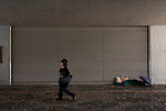 A homeless person uses an umbrella to shield themselves against winter draft as they sleeps under a bridge near the Tokyo Metropolitan Government building in Shinjuku, Tokyo, Japan. Saturday, November 28th 2009