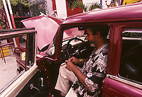 Cuban muralist Salvador Gonzales in his 1955 Mercury in Havana, Cuba in 1998. Gonzalez is one of Cuba's foremost contemporary painters and has incorporated his Central Havana neighborhood into a gigantic mural, part of which can be seen behind him.