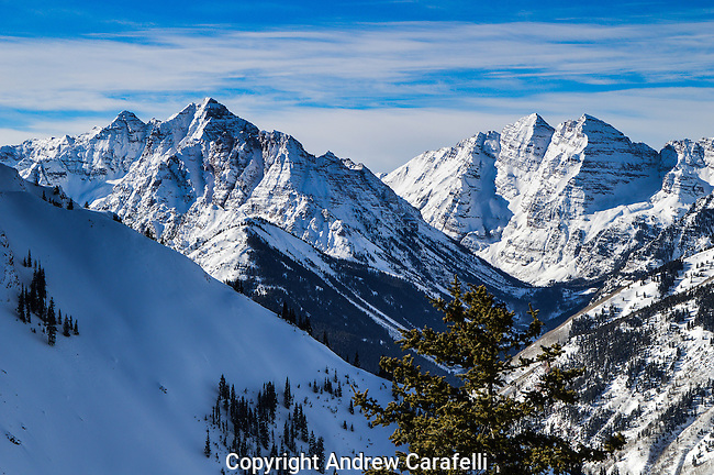 """Three of Colorado 's famous 14,000 foot peaks march in review. 14,026 foot high Pyramid Peak in the foreground  and 14,156 foot high Maroon Peak and 14,012 North Maroon Peak  behind, collectively known as the """"Maroon Bells"""""""