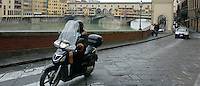 A scooter zips along the river in Florence, Italy March 1, 2006. (Photo by Alan Greth)