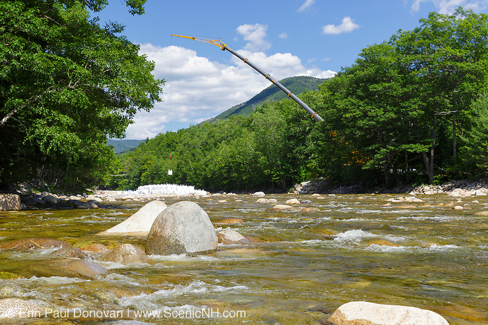 A crane places large sandbags into the East Branch of the Pemigewasset River in Lincoln, New Hampshire USA during the summer months. The sandbags are being used to divert water away from an area along the river that workers will be working in.