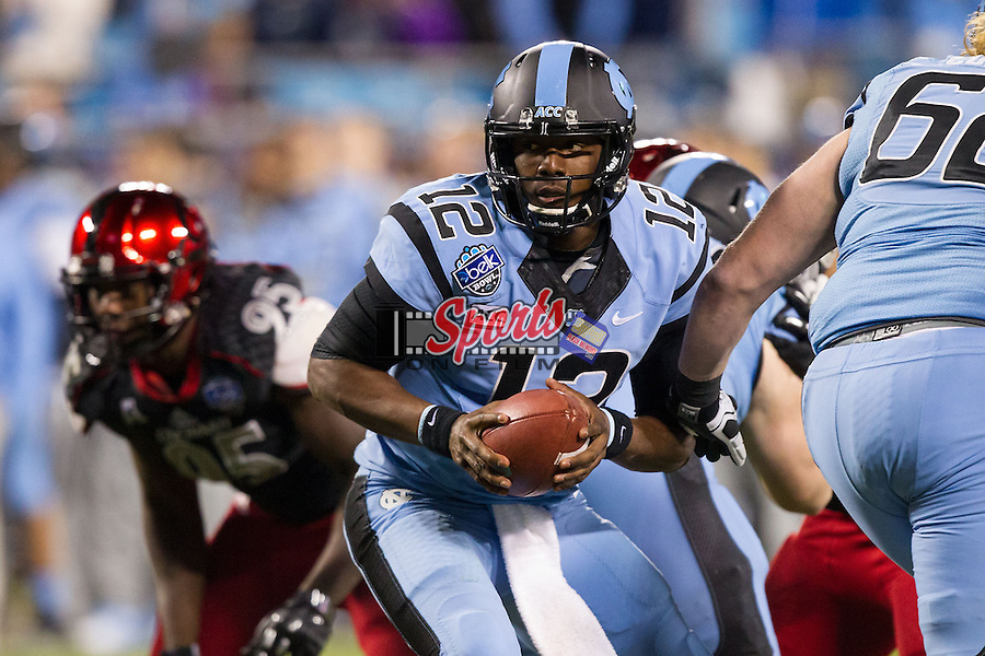 Marquise Williams (12) of the North Carolina Tar Heels looks to hand the ball off against the Cincinnati Bearcats in the Belk Bowl at Bank of America Stadium on December 28, 2013 in Charlotte, North Carolina.  The Tar Heels defeated the Bearcats 39-17.   (Brian Westerholt/Sports On Film)