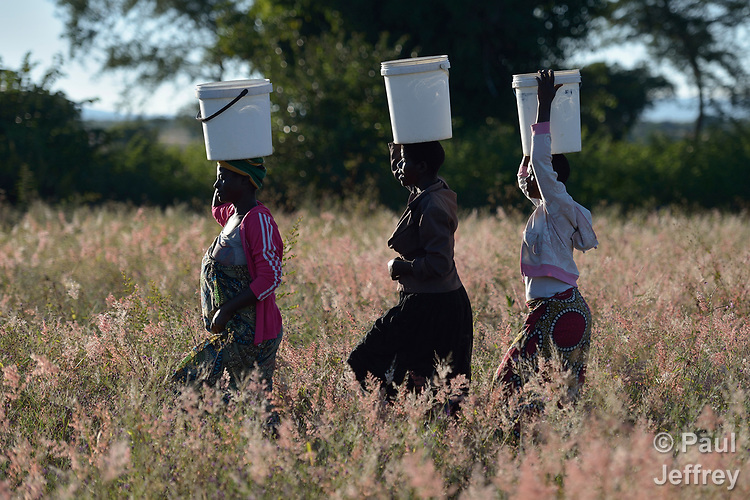 Misuzi Tembo (left) carries water to her home in Kayeleka Banda, Malawi, accompanied by her sisters Chimwemwe Kumwenda and Rhoda Nyoni. Pregnant with her first child, Tembo receives support from the Maternal, Newborn and Child Health program of the Livingstonia Synod of the Church of Central Africa Presbyterian. Tembo's husband has a job in South Africa and sends home money to support her.