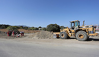 Pictured: A digger operates near forensic officers and volunteers at the second site in Kos, Greece. Sunday 16 October 2016<br />