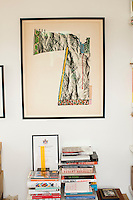 A modern artwork hangs on the wall above a stack of books.