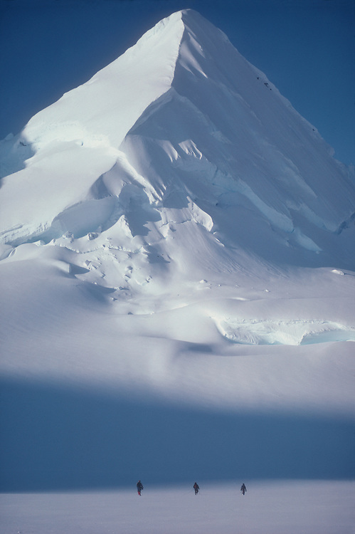 Alaska, mountain climbing, Chugach Range. Matanuska Glacier, Three roped climbers from the National Outdoor Leadership School approach a lone, snow covered, classically shaped mountain horn..