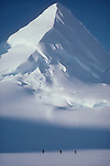 Alaska, mountain climbing, Chugach Range. Matanuska Glacier, Three roped climbers from the National Outdoor Leadership School approach a lone, snow covered, classically shaped mountain horn..