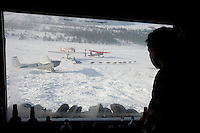 Tuesday March 6, 2007   Rainy Pass checkpoint---- Iditarod Pilot Danny Davidson watches from inside a cabin as a team glides through the parked airplanes, including his, as it leaves  the Rainy Pass checkpoint on Tuesday morning