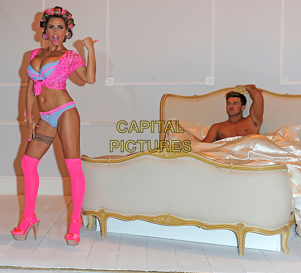 Katie Price (Jordan) & Leandro Penna.The launch photocall for Katie Price's new summer lingerie range for Store 21, The Worx, London, England..May 29th, 2012.full length pink lace top knotted bra cleavage belly stomach midriff knickers underwear tights stockings tattoo garter beige platform sandals shoes rollers curlers in hair side bed chest topless couple hand thumb pointing mouth open  arm in air smiling.CAP/DH.©David Hitchens/Capital Pictures.