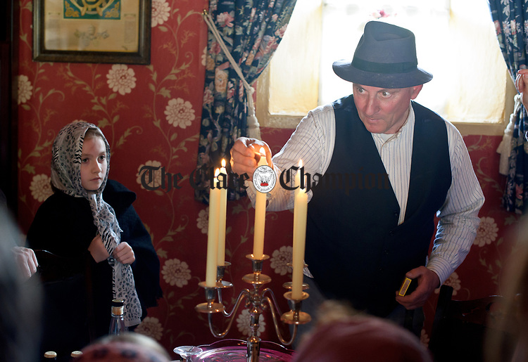 "Paul Markham, ""Fear An Ti"" lights up the candles in the parlour in honour of his special guests during a cultural visit to The Rambling House in Kilmurry Mc Mahon by pupils of Labasheeda National School. Photograph by John Kelly."
