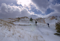 A backcountry skier and snowshoer crosses the snow covered Grand Sable Dunes as a snow squall moves over Lake Superior in Pictured Rocks National Lakeshore.