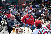 People eat while waiting outside Fenway Park for the start of the 2011 season opening game of the Boston Red Sox in Boston, Massachusetts, USA.