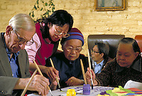 SENIORS AND ASIAN AMERICAN THERAPIST IN A DAYCARE TREATMENT CENTER. ART THERAPY. SENIORS AND THERAPIST. SAN FRANCISCO CALIFORNIA.